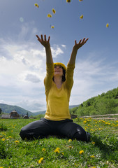 Young woman throws yellow flowers in the air