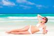 Beautiful woman in white bikini on the beach. Travel concept