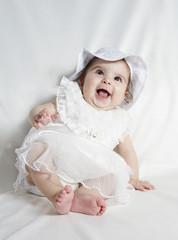 beyaz elbiseli gülen bebek