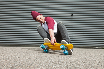 Street skateboarder with woolen cap doing trick on street in fro