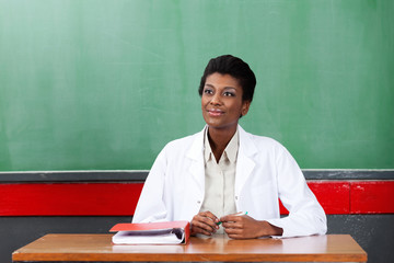 Thoughtful Female Teacher Sitting At Desk In Classroom