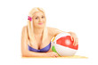 Beautiful blond female lying on a beach towel and holding a ball