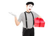Male mime artist holding a gift box and gesturing with his hand