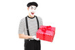 Male mime artist holding a gift box and looking at camera