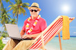 Mature male tourist sitting on a sun lounger and working on a la