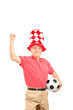 Mature sport fan with hat holding a ball and gesturing happiness