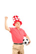 Mature sport fan with hat holding a soccer ball and gesturing ha
