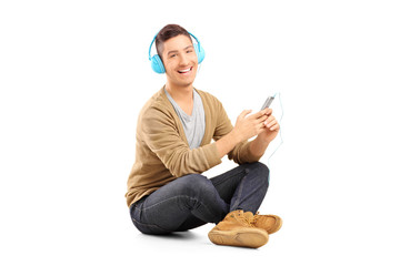 Guy sitting on a floor and listening music on headphones from hi