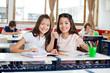 Happy Schoolgirls Gesturing Thumbs Up At Desk