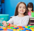 Girl Playing With Construction Blocks With Friends In Background