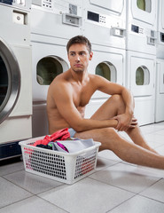Bored Man With Laundry Basket Waiting To Wash Clothes