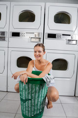 Woman With Clothes Basket In Laundromat