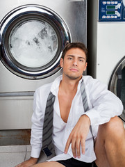 Businessman Sitting In Front Of Washing Machines