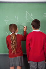 Teenage Students Solving Mathematics On Board