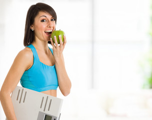 Fit woman eating a green apple
