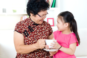 Asian little girl presenting tea to grandmother