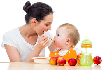 young mother feeding her daughter girl