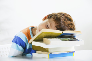Tired schoolboy studying in home.