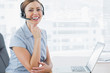 Laughing call centre agent wearing headset at her desk