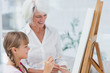 Cheerful grandmother and granddaughter painting together