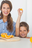 Little boy raising an orange segment