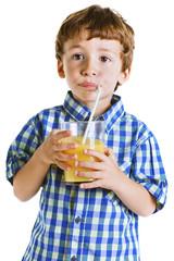 Child with plaid shirt drinking a fresh orange juice.
