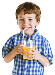 Child with plaid shirt drinking a fresh orange juice.