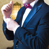 Close-up of a man in a tux fixing his cufflink poster
