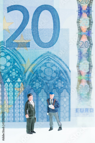 Miniature men strolling with twenty Euro banknote background