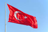Turkish flag and flagpole against blue sky