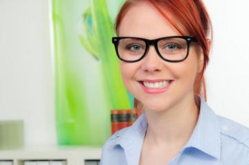 rothaarige junge frau mit brille