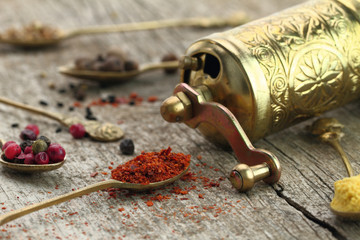 Old spoons with spices and pepper grinder on wooden background