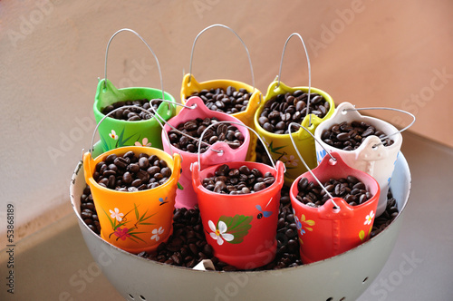 Coffee beans in mini colorful earthenware bucket.