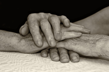 Old people hold each others hands.