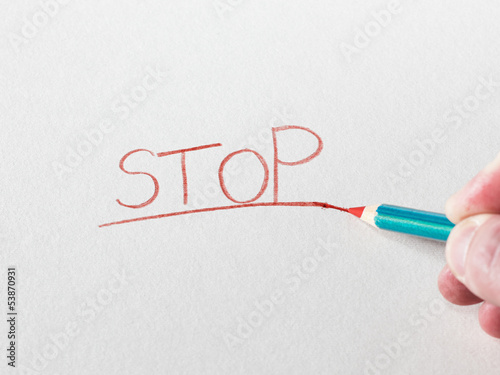 Pastel pencil writing the word Stop.