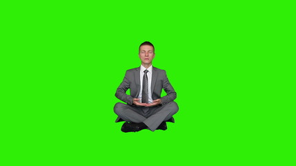Young businessman meditating, Green Screen