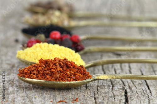 Old spoons with spices on wooden background