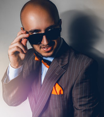 Beautiful man in sunglasses looking away on gray background