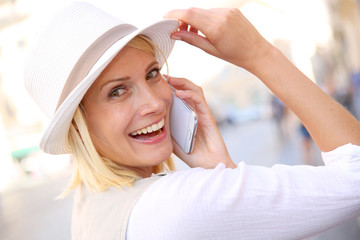 Beautiful blond woman with hat talking on the phone