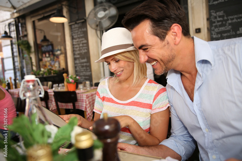 Happy couple of tourist sitting at restaurant table in Rome