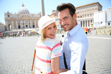 Cheerful couple standing by Saint Peter's Basilica of Rome