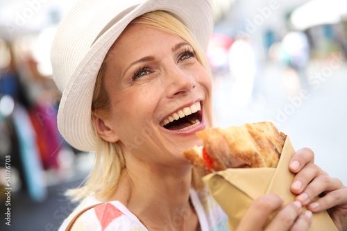 Cheerful blond girl in Rome eating Focaccia sandwich