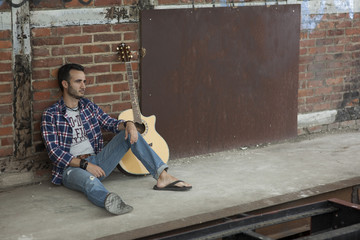 Man with guitar sitting on the floor