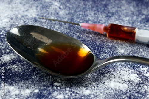Drug syringe and spoon with white powder