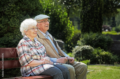canvas print picture aged couple sitting on a bench in a cemetery