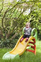 kleines Mädchen im Garten auf der Rutsche
