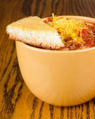 Cup of chili with cornbread and sprinkle of cheddar cheese