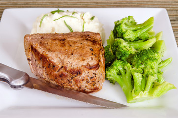 Pan-fried top sirloin filet steak with broccoli and mashed potat
