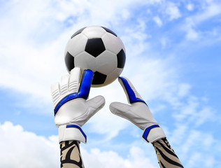 Soccer goalkeeper's hands reaching for the ball, with net and sk