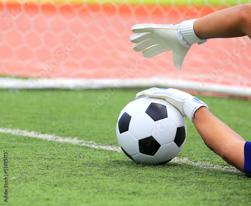 Soccer goalkeeper's hands reaching for the ball, with net